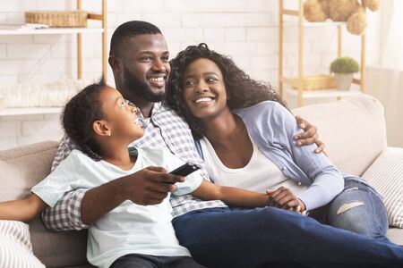 Photo pour Happy black family of three watching tv, relaxing together at home, enjoying weekend together. - image libre de droit