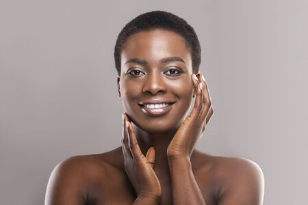 Photo pour Beautiful black woman with short hair touching her smooth cheeks, applying cream or lotion on face and looking at camera, copy space - image libre de droit