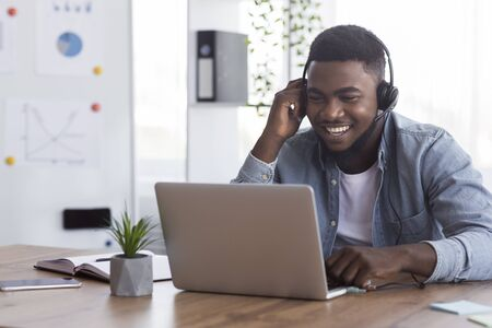 Photo pour Cheerful african american worker wearing headphones, watching webinar on laptop in office - image libre de droit