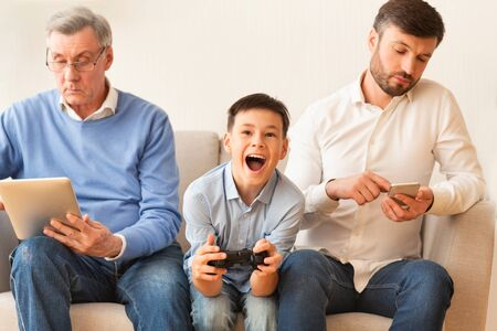 Photo pour Modern Lifestyle. Boy Playing Video Game Sitting Between Indifferent Grandfather And Father At Home. Selective Focus - image libre de droit