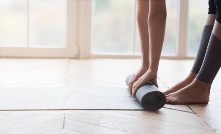 Photo for Cropped image of woman hands and legs, rolling sport mat at studio, panorama with copy space - Royalty Free Image
