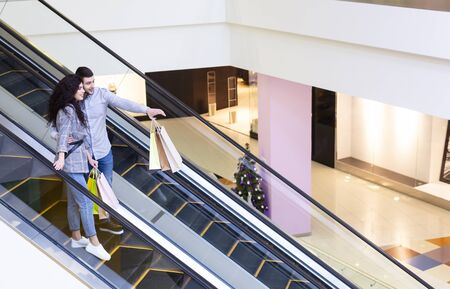 Photo pour Sale and consumerism. Couple going down by escalator and pointing finger in mall, free space - image libre de droit