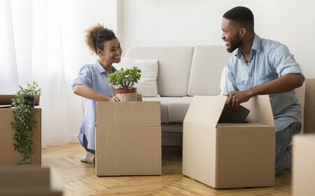 Photo pour Moving Apartment. Happy Black Spouses Packing Stuff In Cardboard Boxes Sitting On Floor Indoor. Selective Focus - image libre de droit