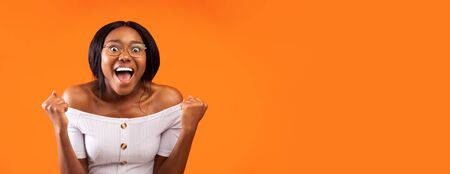 Happy Black Woman Screaming Shaking Fists Celebrating Success Standing Over Orange Studio Background. Panorama, Empty Space