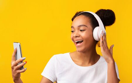 Photo pour Cheerful African American Teen Listening To Favorite Music With Wireless Headphones, Yellow Background - image libre de droit
