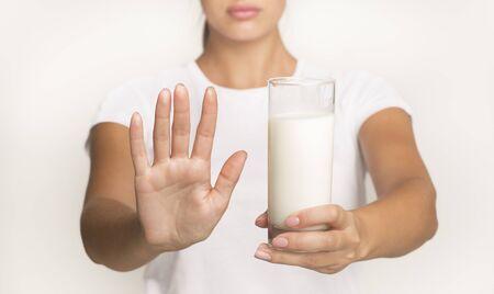 Photo pour Lactose Intolerance Concept. Unrecognizable Woman Holding Milk And Gesturing No Standing In Studio On White Background. Cropped - image libre de droit