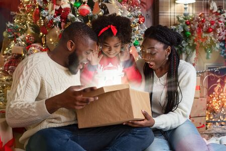 Foto de Excited african american family of three opening shining gift box in living room near Xmas tree, celebrating holidays at home - Imagen libre de derechos