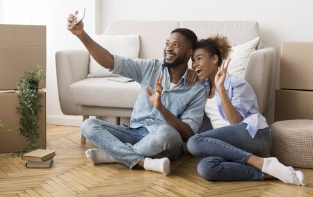 Photo pour Afro Couple Taking Selfie With Smartphone Gesturing Victory Sign After Moving Into New Home. Copy Space - image libre de droit