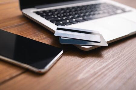 Photo pour Smartphone with blank screen, laptop and credit cards flat laying on wooden table, closeup - image libre de droit