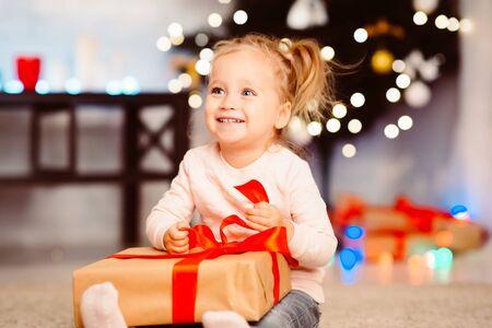 Photo pour Adorable happy little girl enjoying Christmas gift, empty space - image libre de droit