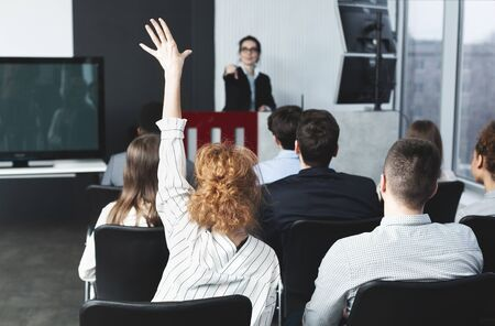 Foto de Businesswoman raising hand at seminar, female speaker pointing at woman - Imagen libre de derechos