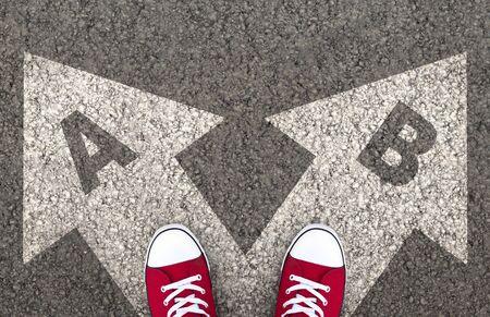 Foto de Dillema Concept. Shoes standing on asphalt road with two arrows to plan A and B. Top view. - Imagen libre de derechos