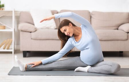 Pregnant Woman Stretching Arms And Legs, Doing Prenatal Workout At Home On Yoga Mat. Selective focus