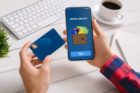 Photo pour Man using smartphone with digital wallet application making payment from credit card at workplace in office, closeup - image libre de droit