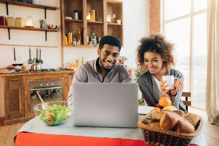 Foto per Happy african-american couple using laptop at kitchen, planning wedding and honeymoon., panorama, copy space - Immagine Royalty Free
