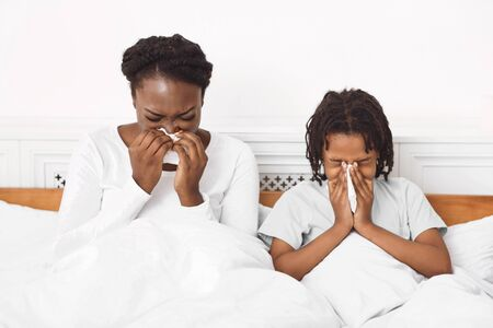 Photo for Allergy Symptoms. Unhappy afro family using paper tissues while blowing nose and sneezing - Royalty Free Image