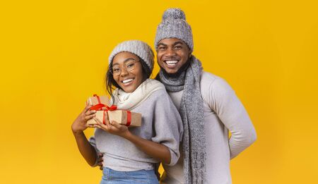 Photo for Christmas, new year gifts. Winter black couple in knitted hats holding Xmas gifts, yellow background, panorama with copy space - Royalty Free Image