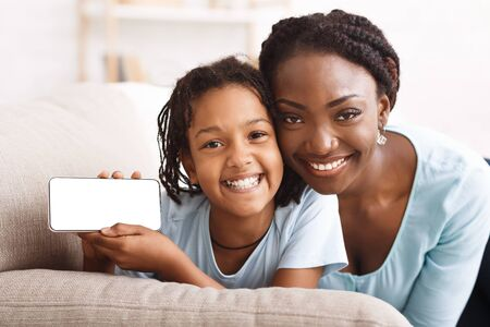 Photo pour Mockup Image Of Black Girl Holding And Showing White Mobile Phone With Blank Screen At Home With Her Mom - image libre de droit