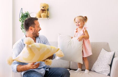 Photo for Family Morning Concept. Playful dad and daughter having a pillow fight together in the bedroom - Royalty Free Image