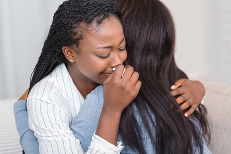 Foto de Friendship and consoling. Unrecognizable black woman hugging her crying friend at home, comforting and expressing support, closeup - Imagen libre de derechos