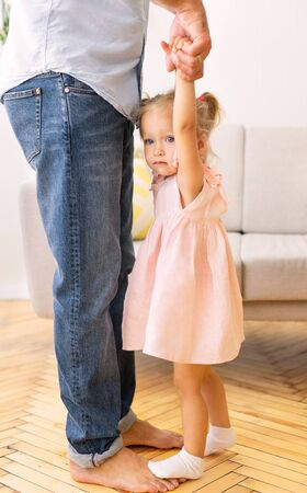 Photo pour Cropped Image Of Dad And Daughter Dancing At Home. Adorable little girl standing on fathers feet - image libre de droit