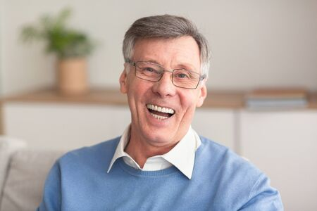Photo pour Old Age Happiness. Cheerful Senior Man Laughing Looking At Camera Sitting On Couch At Home. - image libre de droit