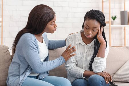 Photo pour Friendship And Support. Compassionate Black Girl Comforting Her Upset Friend, Soothing Her After Breakup With Boyfriend, Sitting On Sofa At Home. - image libre de droit
