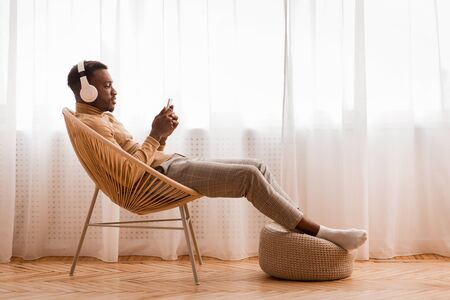 Photo for Weekend. Relaxed Black Man In Wireless Headset Using Mobile Phone Listening To Audiobook Sitting On Modern Chair Against Window Indoor - Royalty Free Image