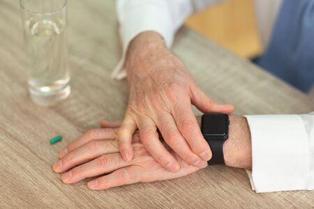 Photo pour Medication Schedule. Unrecognizable Senior Man Checking Time With Smartwatch Before Taking A Pill. Closeup, Cropped - image libre de droit