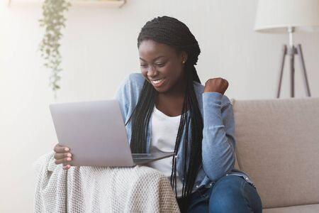 Foto de Successful frelancer. Excited african american woman celebrating success with laptop on sofa at home. - Imagen libre de derechos