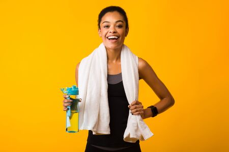 Photo pour Fitness Lifestyle. Cheerful African American Woman Holding Bottle Of Water Smiling At Camera Standing In Studio On Yellow Background. - image libre de droit