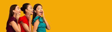 Foto de Secrets Splitting. Three Glamorous Girls Gossiping Whispering Sharing News Standing In Studio Over Yellow Background. Panorama, Copy Space - Imagen libre de derechos