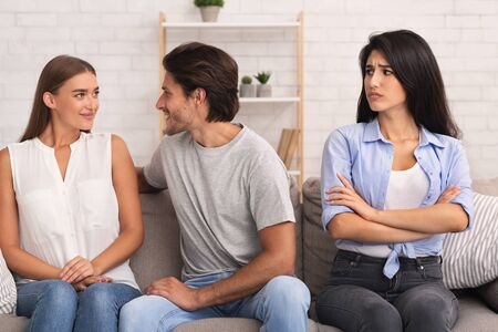 Photo pour Jealousy And Cheating. Sad Girl Looking At Her Boyfriend Flirting With Another Woman Sitting On Sofa At Home. - image libre de droit