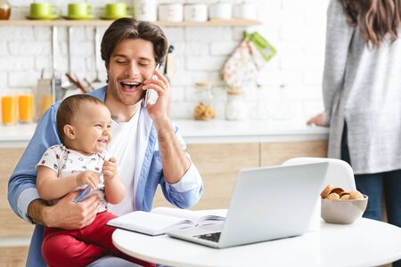 Photo pour Working on weekends. Cheerful dad consulting clients by phone, working with cute baby son at home kitchen, free space - image libre de droit