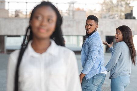 Photo pour Distracted african american guy turning around and looking to another woman while walking with his girlfriend - image libre de droit