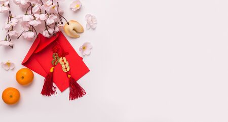 Foto de Chinese New Year festival concept. Sakura with mandarins and red envelopes with congratulations, white background, copy space, panorama - Imagen libre de derechos