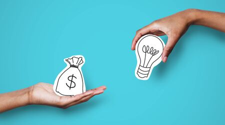 Photo for Startup supporting. Hands with dollar sign bag and light bulb over blue background, investor giving creator money - Royalty Free Image