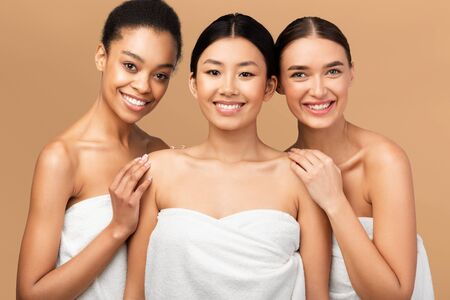 Photo pour Beauty And Skin Care. Three Diverse Women In Bath Towels Smiling At Camera Posing Over Beige Background. Studio Shot - image libre de droit