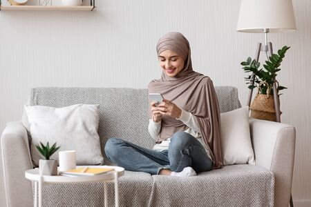 Photo pour Smiling muslim girl in headscarf using smartphone at home, messaging or browsing social networks, relaxing on couch in living room, copy space - image libre de droit