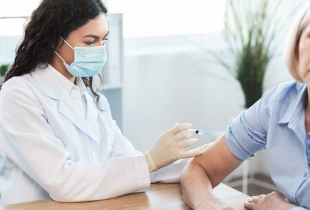 Photo for Seasonal Flu Shot. Mexican doctor in medical mask injecting tetanus toxoid vaccine to mature woman, copy space - Royalty Free Image