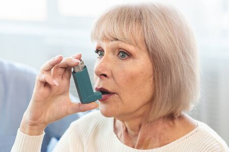 Photo pour Senior Woman Using Asthma Inhaler For Allergies In Modern Clinic, Copy Space - image libre de droit