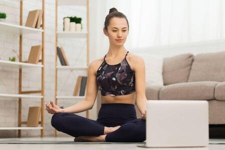 Photo pour Millennial woman practicing yoga at home, using laptop, free space - image libre de droit