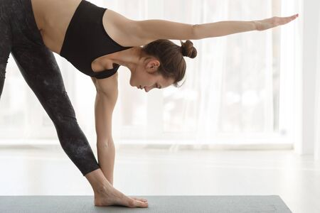 Photo pour Morning practice. Girl making triangle yoga pose at studio with panoramic windows - image libre de droit