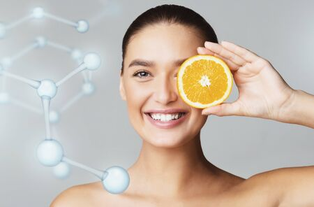 Photo pour Happy young beautiful woman covering eye with orange half over grey background, molecular model, modern beauty industry concept - image libre de droit