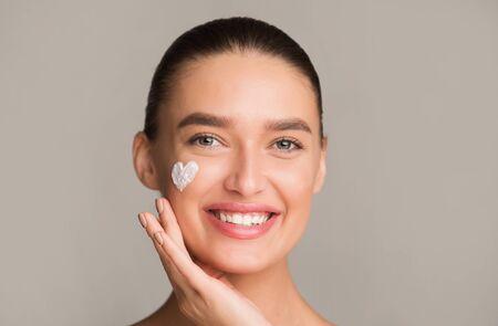 Photo pour Skin hydration. Positive girl applying moisturizing cream in heart shape on cheek, grey background - image libre de droit