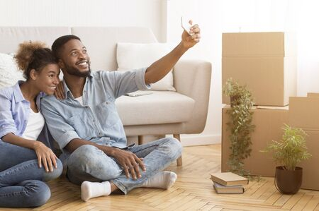 Photo pour Happy Black Couple House Owners Making Selfie On Phone After Moving Into New Apartment. Free Space For Text - image libre de droit