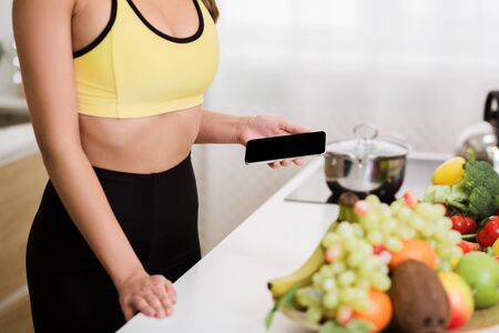 Photo for Woman using phone calculating calories on kitchen after training, choosing what to eat - Royalty Free Image