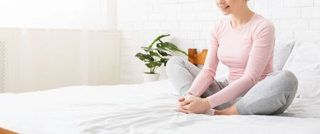 Foto de Home pilates. Young woman doing butterfly exercise for legs in bed, panorama with empty space - Imagen libre de derechos