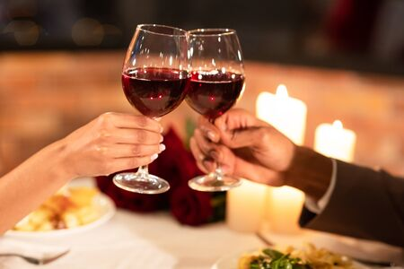 Photo pour Date In Restaurant. Unrecognizable Boyfriend And Girlfriend Clinking Glasses Drinking Red Wine During Romantic Dinner Indoor. Closeup, Cropped - image libre de droit