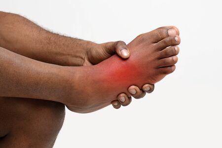 Foto de Cropped of black man holding his painful foot, cramp, muscular spasm, red accent on sore zone - Imagen libre de derechos